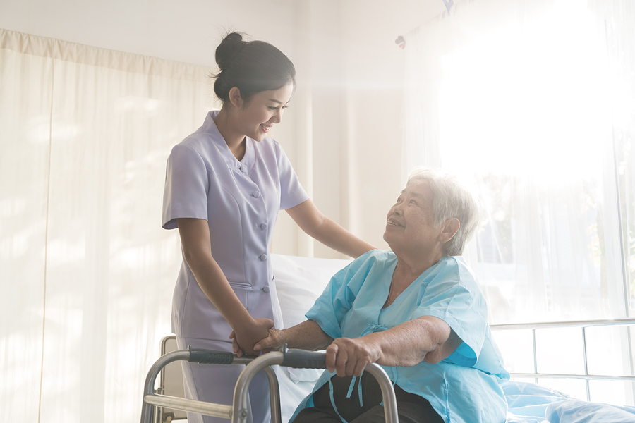 Asian young nurse supporting elderly patient disabled woman in using walker in hospital. Elderly patient care concept.