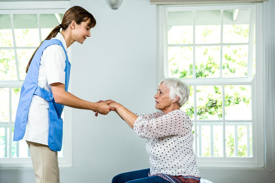 Nurse assisting senior woman at health club
